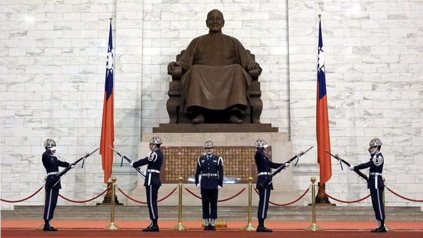 Taiwanese soldiers perform a changing of the guard ceremony before a statues of late President Chiang Kai-shek at the Chiang Kai-shek Memorial Hall in Taipei on Dec. 6, 2017.