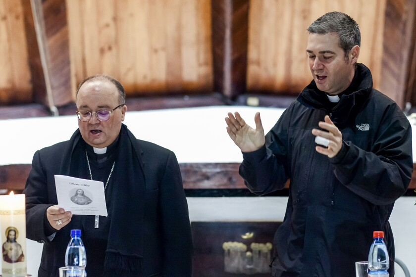 FILE - Archbishop Charles Scicluna, left, and Spanish Monsignor Jordi Bertomeu attend a meeting with the Catholic community at the Sacred Heart of Jesus church in Osorno, Chile, in this Saturday, June 16, 2018 file photo. The Vatican is sending its top two sex crimes investigators to Mexico on a fact-finding and assistance mission as the Catholic hierarchy in the world's second-largest Catholic country begins to reckon with decades of clergy sex abuse and cover-up. (AP Photo/Fernando Lavoz)