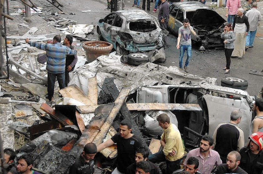 Residents and police inspect the scene of a car bombing in Homs this week. In Homs' Old City, Syrian officials have been pressing rebels to lay down their arms in exchange for limited amnesty, while rebels have pressed instead for safe passage out of the district.