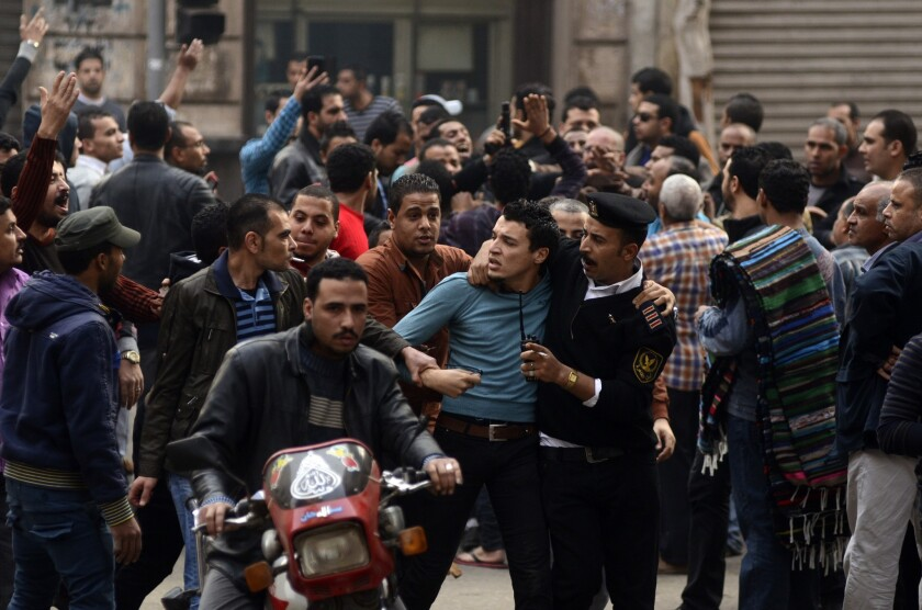 A supporter of ousted Egyptian president Mohamed Morsi is detained by police during clashes with security forces.