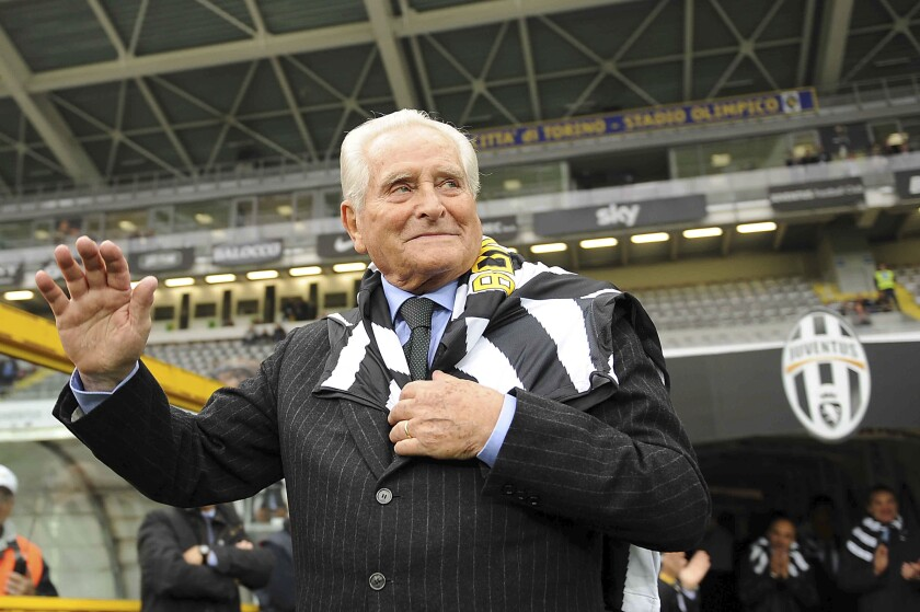Former Juventus player and president Giampiero Boniperti waves as he wears a Juventus scarf during a Serie A soccer match between Juventus and Cesena, in Turin, Italy, in this Nov. 6, 2010 photo. The Italian soccer federation announced Friday, June 18, 2021 that Boniperti passed away overnight at the age of 92. (Fabio Ferrari/LaPresse via AP)
