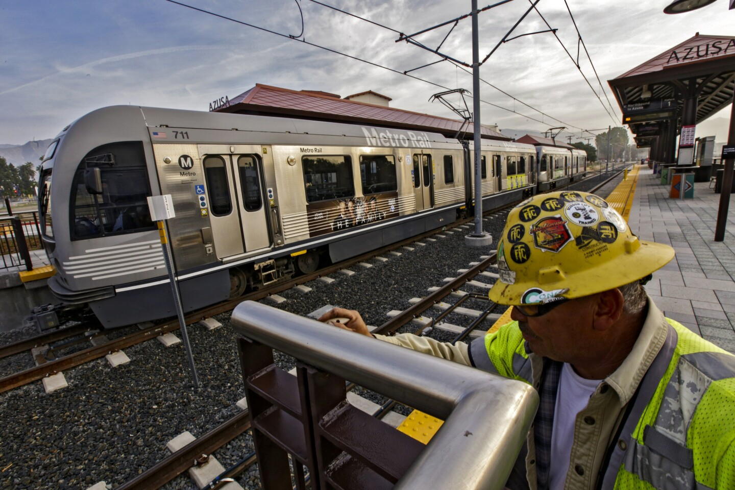 Lino Cabriales does a last-minute paint touch-up as a Metro Gold Line train leaves the new Azusa station on a test run. The 11.5-mile Foothill Extension, taking the Gold Line deeper into the San Gabriel Valley, opens Saturday.