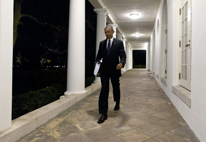 After and evening meeting, President Barack Obama walks along the colonnade from the Oval Office to the White House Residence in Washington, Friday, Feb. 19, 2016, carrying a binder containing information on possible Supreme Court nominees. (AP Photo/Carolyn Kaster)