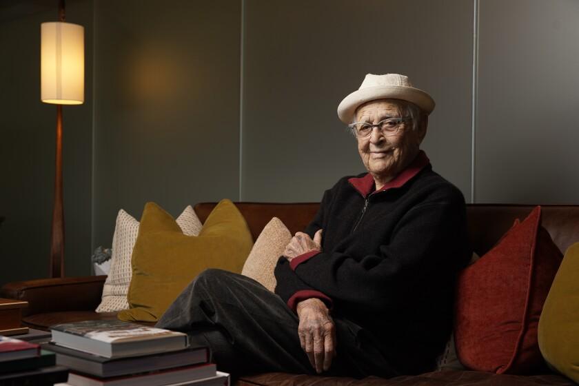 Norman Lear sitting on a sofa