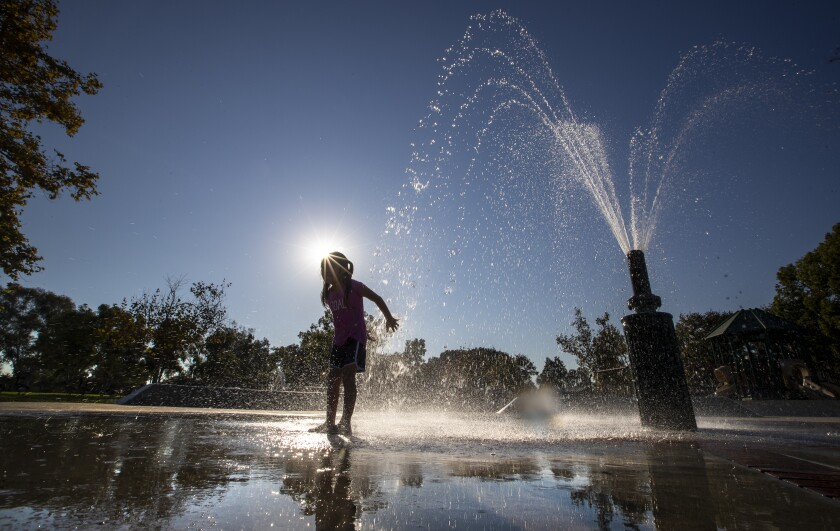 Brittany Castro, 5, of Santa Ana, plays in a splash pool at Mile Square Regional Park in Fountain Valley on Tuesday