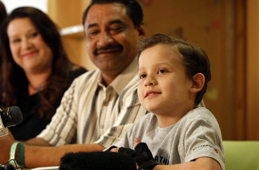 Luke Acuna takes a question during a news conference Thursday at Rady Children's Hospital, where he has been hospitalized since being hit by a trash truck while skateboarding in November. Luke lost his left leg after the crash. Beside him are his parents, Anthony and Dawneva Acuna.