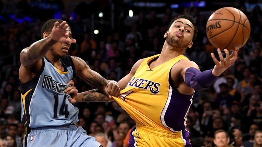 Lakers guard D'Angelo Russell tries to catch a pass while battling Grizzlies guard Xavier Munford for position during their game Tuesday.