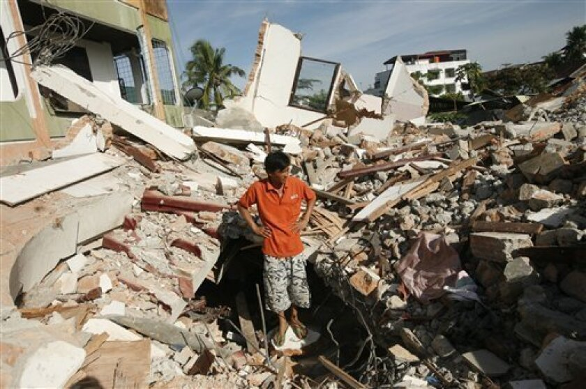 An Indonesian man stands on the ruins of his house flattened by an earthquake in Padang, West Sumatra, Indonesia, Thursday, Oct. 8, 2009. The 7.6 magnitude temblor devastated a stretch of more than 60 miles (100 kilometers) along the western coast of Sumatra island last week. (AP Photo/Dita Alangkara)