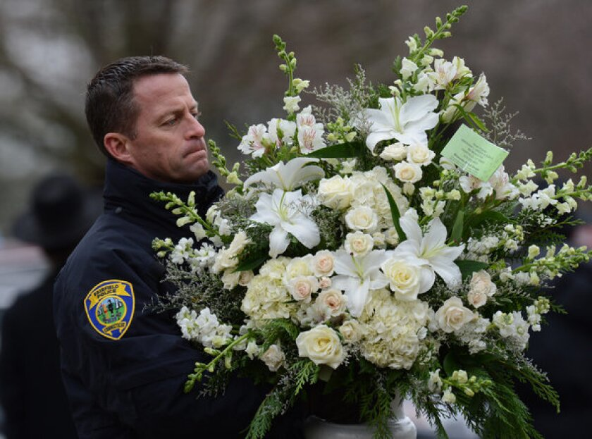 A police officer helps move floral arrangements after the funeral Monday of a boy who died in the shooting at Sandy Hook Elementary School. Shares of gun makers have tumbled in the wake of the tragedy.