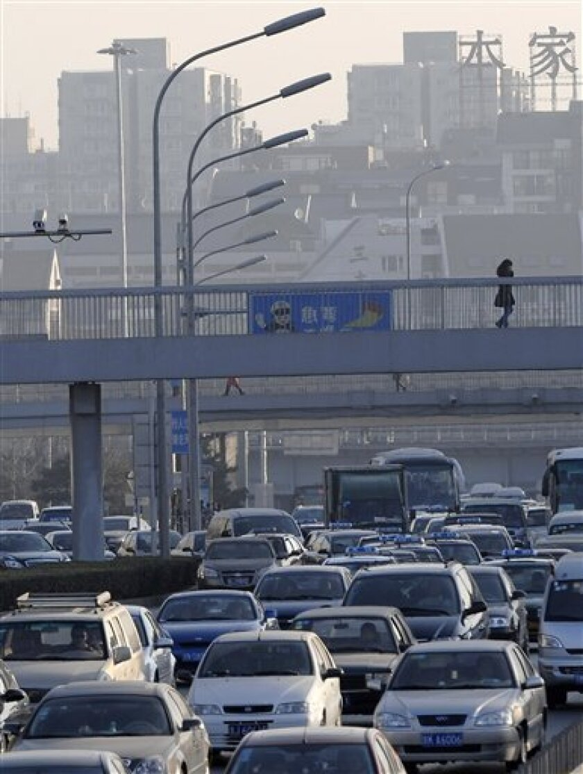 A woman walks on a pedestrian bridge over vehicles getting stuck at a traffic jam in Beijing, China, Tuesday, Dec. 8, 2009. China's auto production and sales more than doubled over a year earlier in November, with both surpassing 1 million vehicles, extending the country's lead over the U.S. as the world's biggest auto market. (AP Photo/Andy Wong)