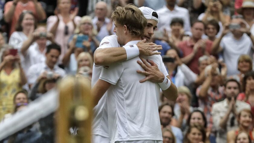 South Africa's Kevin Anderson hugs John Isner of the United States, right, after defeating him in th