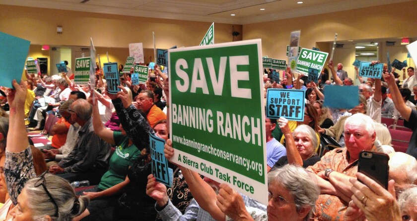 Members of the Banning Ranch Conservancy from Newport Beach, Costa Mesa and Huntington Beach raise signs in support of the California Coastal Commission staff recommendation that the commission deny the Banning Ranch development project during its meeting Wednesday in Long Beach.
