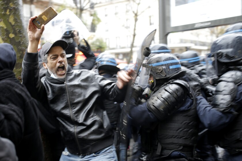 Riot police officers charge a man holding his phone during a protest, Saturday, Dec.12, 2020 in Paris. Protests are planned in France against a proposed bill that could make it more difficult for witnesses to film police officers. (AP Photo/Lewis Joly)