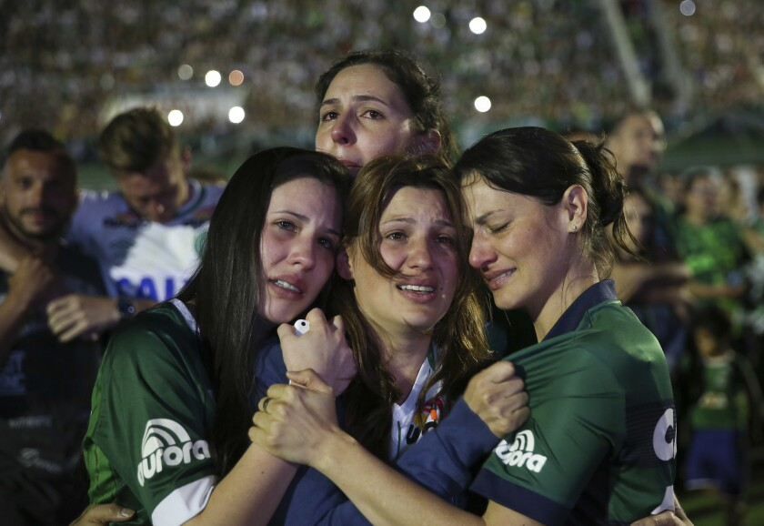 Relatives of Chapecoense soccer players, who died in a plane crash in Colombia, cry during a memorial inside Arena Condado stadium in Chapeco, Brazil, Wednesday, Nov. 30, 2016. Authorities were working to finish identifying the bodies before repatriating them to Brazil. (AP Photo/Andre Penner)