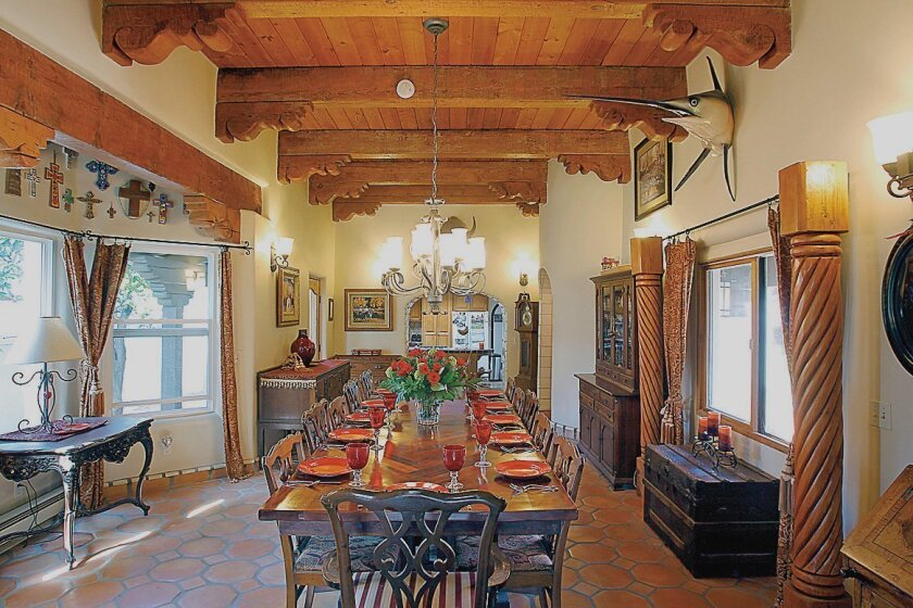 The formal dining room has wood beams from an old Montgomery Ward store. Ron Bosch made the dining table himself, using Honduran mahogany boards from pallets.