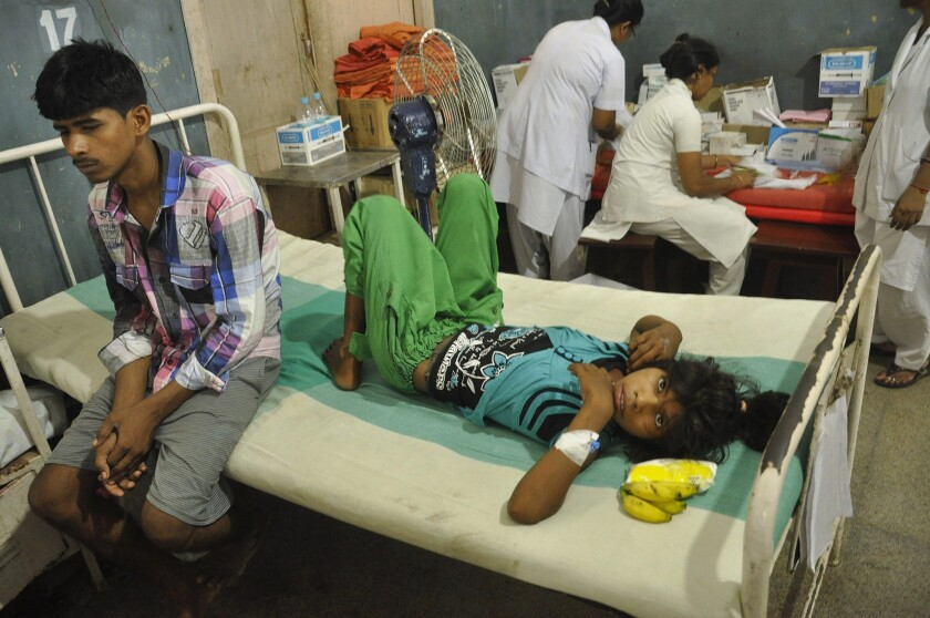 An Indian schoolgirl recovering from food poisoning rests at the Patna Medical College and Hospital.