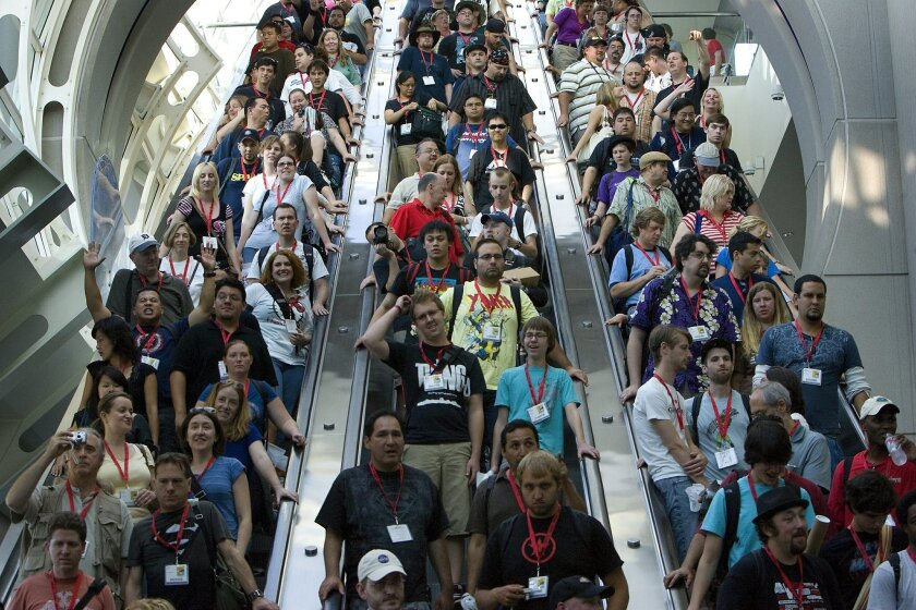 At the San Diego Convention Center, Comic-Con International 2009,  thousands of fans make their way down the escalator toward the main exhibit floor on opening day. Many had waited more than six hours to be the first inside.