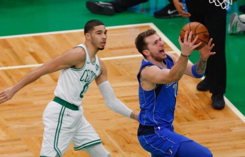 El jugador de Dallas Mavericks Luka Doncic (d) entra a canasta ante Jayson Tatum (I), de Boston Celtics. EFE/EPA