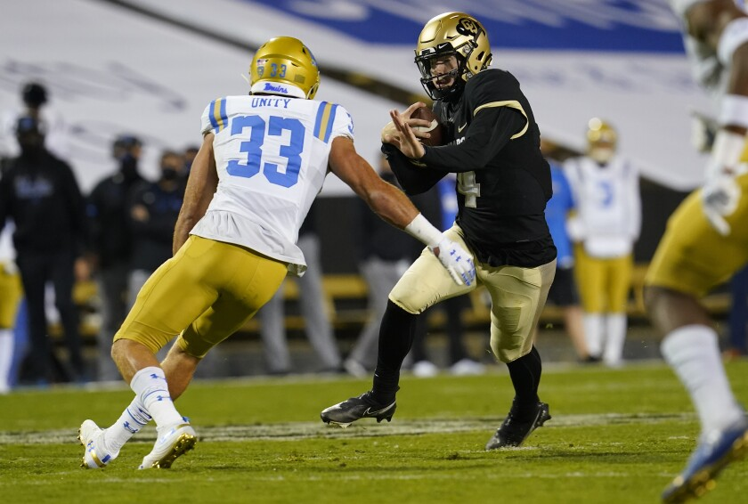 UCLA linebacker Bo Calvert looks to tackle Colorado quarterback Sam Noyer.