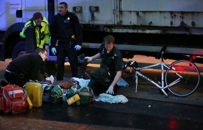 A cyclist receives emergency medical treatment after being involved in a collision with a truck this week in London.
