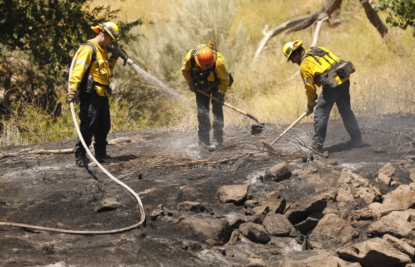 Los Angeles County firefighters work to extinguish flare-ups from the Soledad fire July 6.