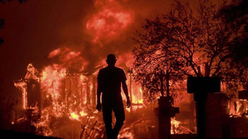 FILE - In this Oct. 9, 2017, file photo, Jim Stites watches part of his neighborhood burn in Fountai