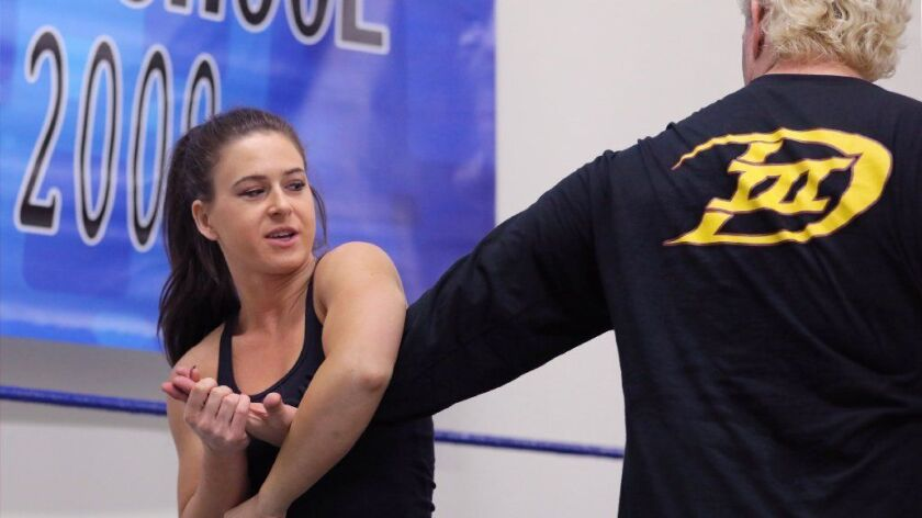 Wrestling student Arkady Unterleidner, left, practices an arm move with veteran pro wrestler Anthony Idol at SoCal Pro Wrestling school's new location in San Marcos. on Monday