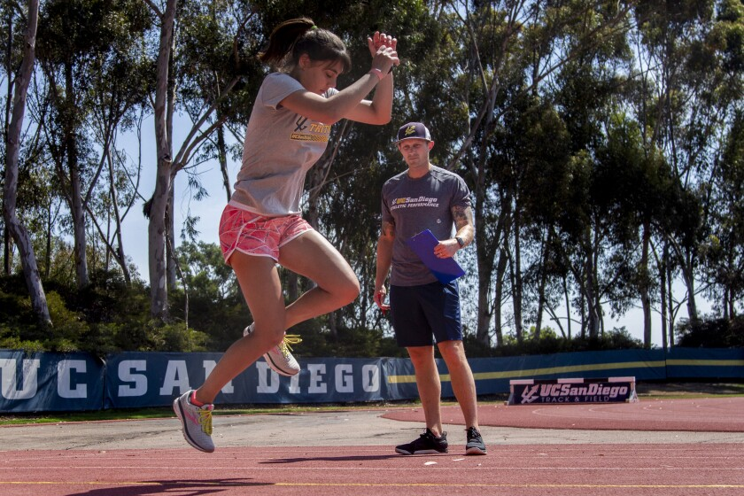 Jenna Mencarelli does track and field drills while Jon Gregory assesses her form