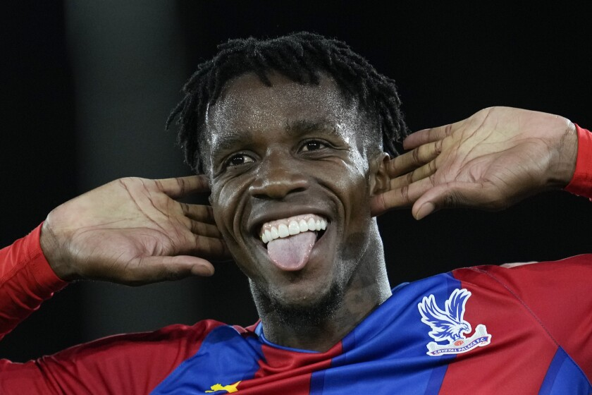 Crystal Palace's Wilfried Zaha celebrates after he scored his side's first goal during the English Premier League soccer match between Crystal Palace and Brighton, at Selhurst Park, London, Monday, Sept. 27, 2021. (AP Photo/Matt Dunham)