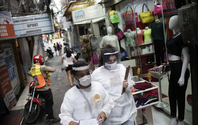 Health workers walk through a slum in Rio de Janeiro to test people for the coronavirus.