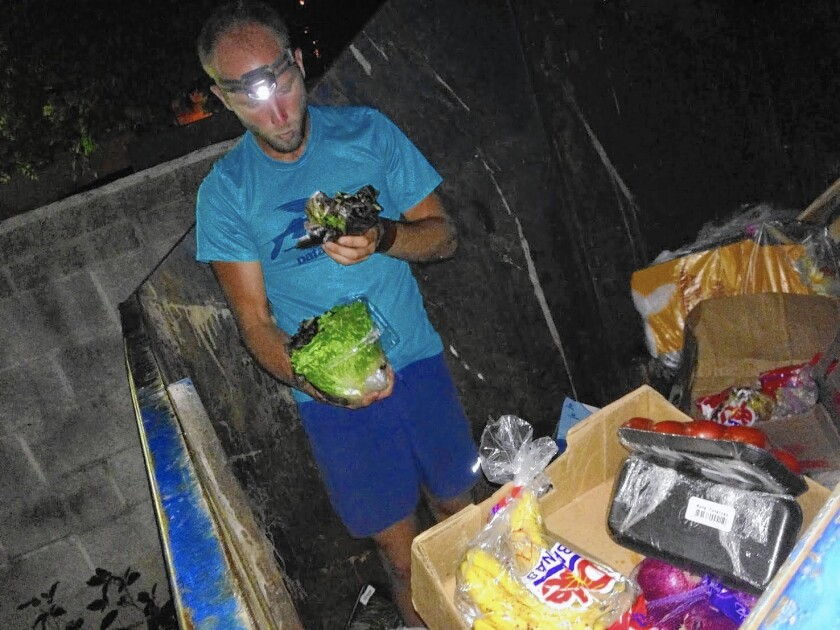 Activist Rob Greenfield inspects the contents of a dumpster near Cleveland, looking for food to put on display for the pubilc in an attempt to raise awareness about how much food is wasted every day.