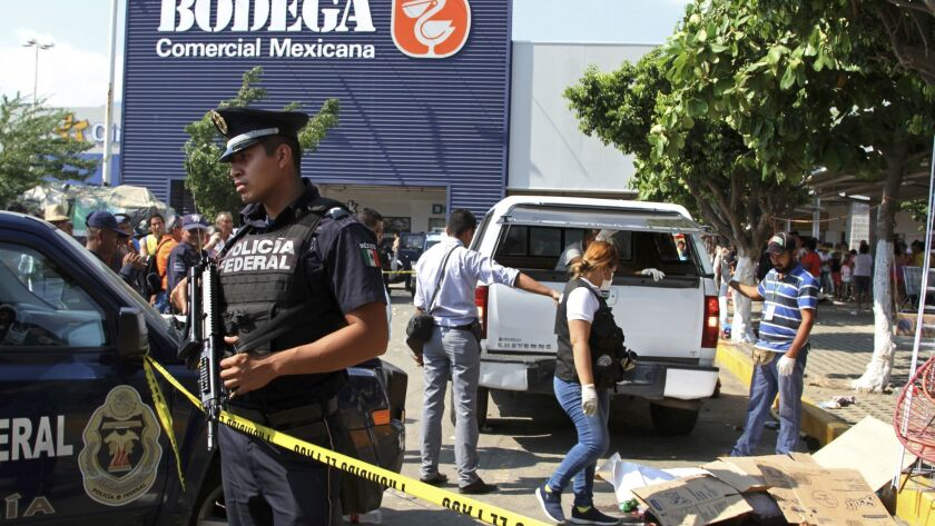 Police and forensics secure an area Jan. 4 in Acapulco, after attackers reportedly got out of a vehicle and began shooting, killing six street vendors.