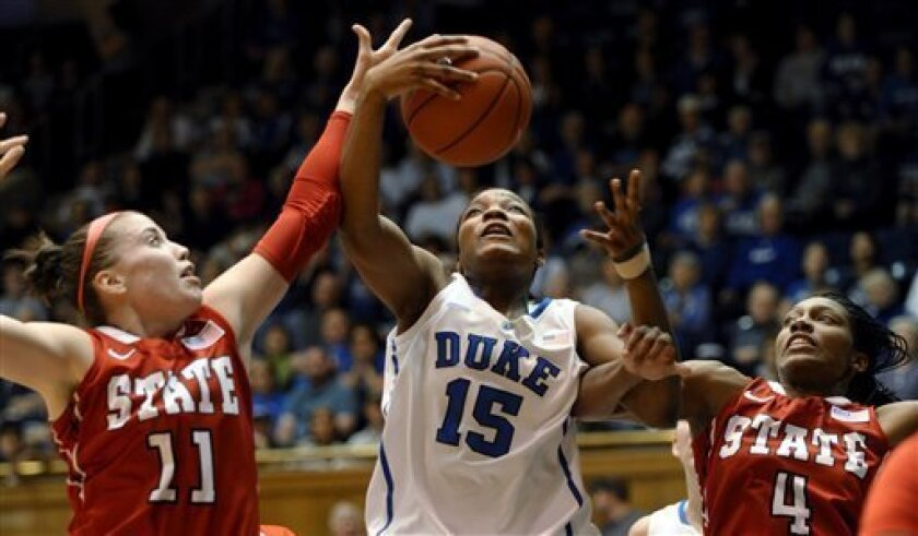 Duke's Richa Jackson (15) reaches for a loose ball between North Carolina State's Emili Tasler (11) and Tia Bell (4) during the first half of an NCAA college basketball game, Sunday, Jan. 8, 2012, in Durham, N.C. (AP Photo/Sara D. Davis)