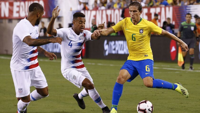 DeAndre Yedlin and Tyler Adams defend Filipe Luís of Brazil during their friendly match at MetLife Stadium on September 7.
