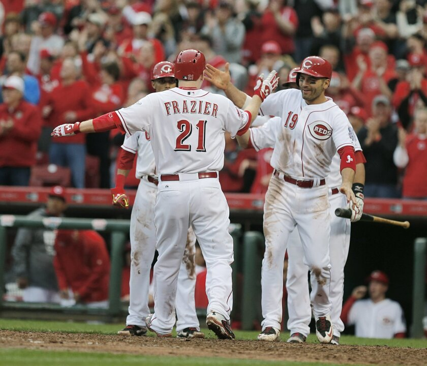 Cincinnati Reds'  Todd Frazier (21), is congratulated at the plate by Joey Votto (19) following a three-run homer off Pittsburgh Pirates' relief pitcher Tony Watson (44) during the eighth inning of their Opening Day baseball game played Monday, April 6, 2015 in Cincinnati. (AP Photo/Gary Landers)