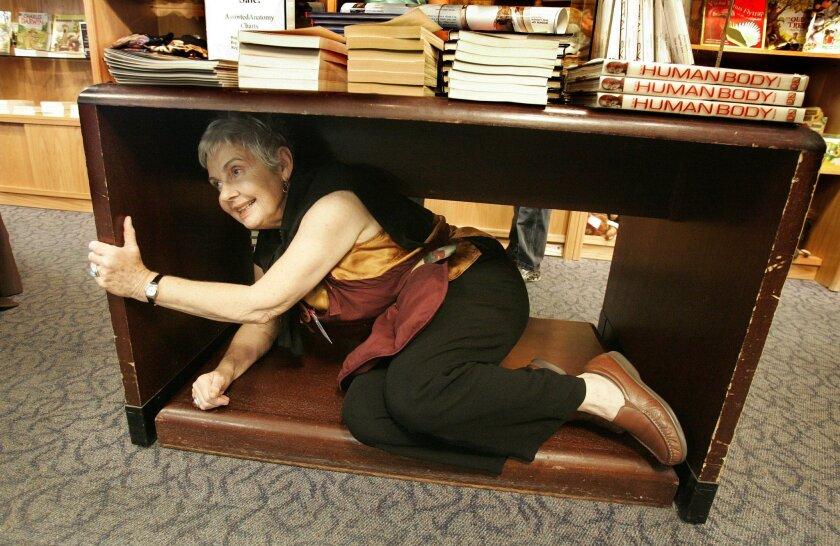 Joy Johnson, an employee of the gift shop at the San Diego Natural History Museum, took cover during yesterday's Great California ShakeOut earthquake preparedness drill. (Earnie Grafton / Union-Tribune)