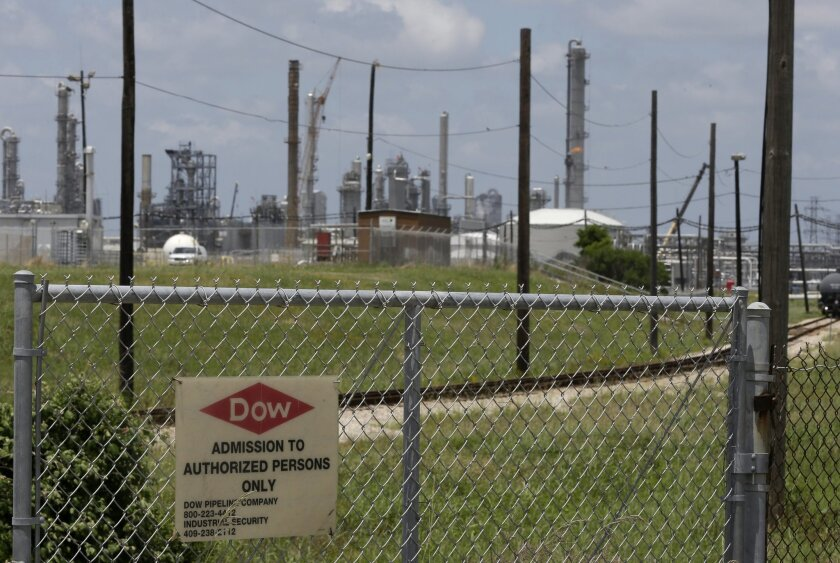 In this May 22, 2014 photo, a sign is posted on a roadside fence outside a Dow Chemicals plant in Freeport, Texas. The plan from Dow Chemical and the Nature Conservancy calls for growing thick groves of trees to capture pollutants downwind from a chemical plant. (AP Photo/Pat Sullivan)