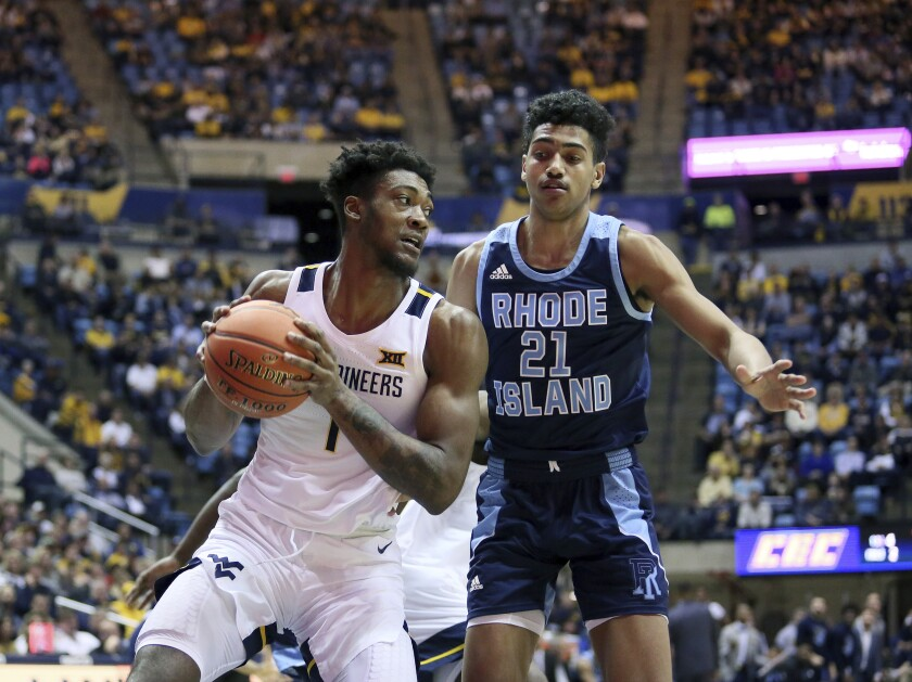 West Virginia forward Derek Culver (1) goes to pass the ball as he is defended by Rhode Island forward Jacob Toppin (21) during the first half of an NCAA college basketball game Sunday, Dec. 1, 2019, in Morgantown, W.Va. (AP Photo/Kathleen Batten)