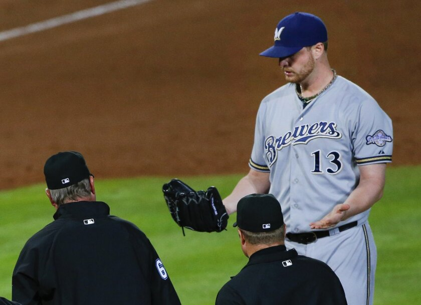 The umpiring crew walk to the mound to talk to Milwaukee Brewers relief pitcher Will Smith before ejecting him in the seventh inning of a baseball game against the Atlanta Braves on Thursday, May 21, 2015, in Atlanta. (AP Photo/John Bazemore)