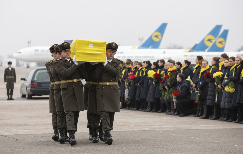 An honor guard carries a coffin of the one of the 11 Ukrainians who were among victims when their plane was shot down by an Iranian missile.