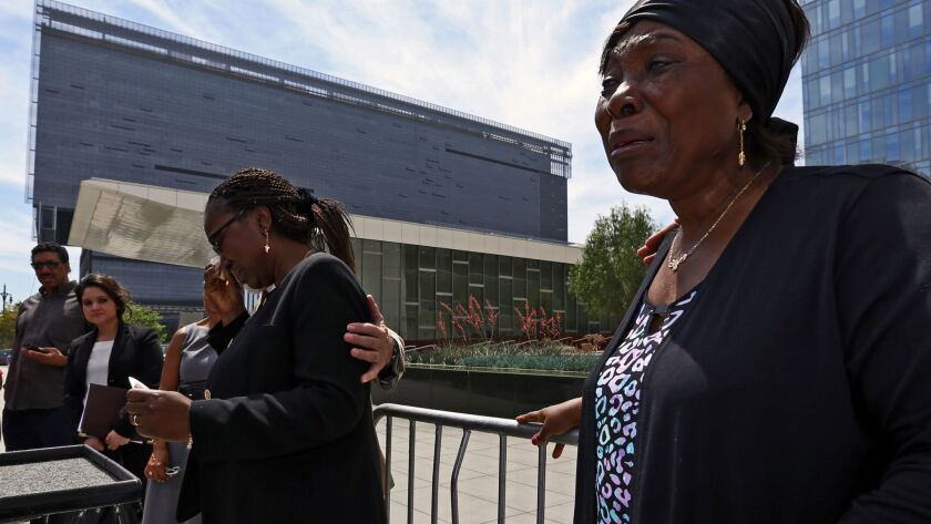 Heleine Tchayou, right, mother of Charly Leundeu Keunang, a homeless man shot and killed by LAPD on skid row, weeps as Keunang's sister Line Marquise Foming addresses a news conference about the family's lawsuit in 2016.