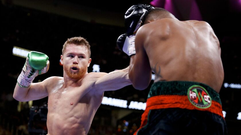 Canelo Alvarez, left, of Mexico, tries to hit Daniel Jacobs with a left during a middleweight title