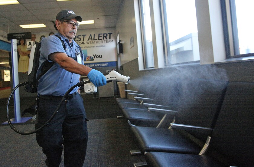 Inside Hollywood Burbank Airport, Isidro Vaca, with Diverse Facility Solutions, sanitizes a waiting area with a Protexus electrostatic backpack sprayer on Friday. The airport is stepping up its sanitation practices to protect passengers from the spread of the coronavirus.