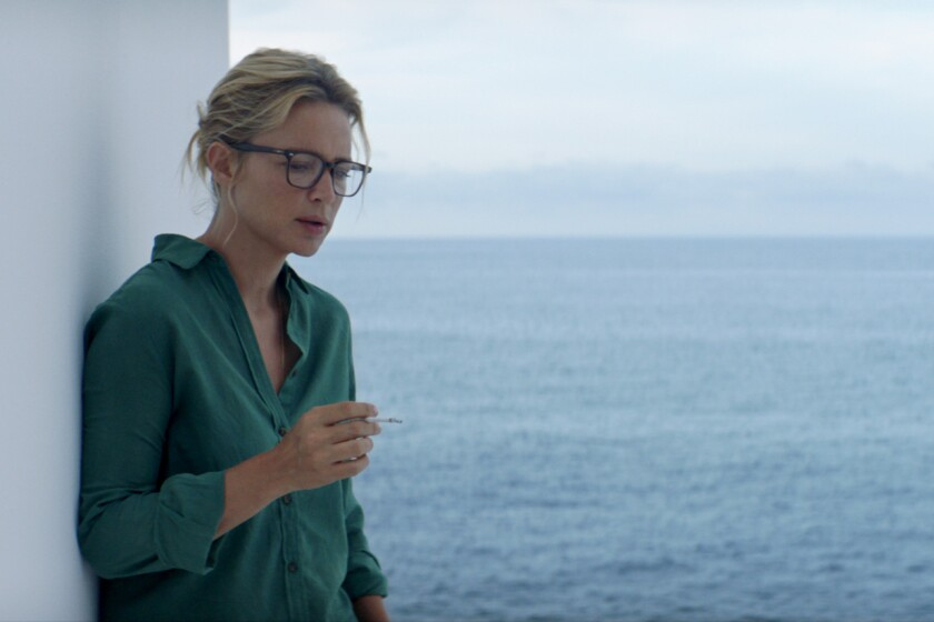 Sybil, played by Virginie Efira, smokes in front of the sea.