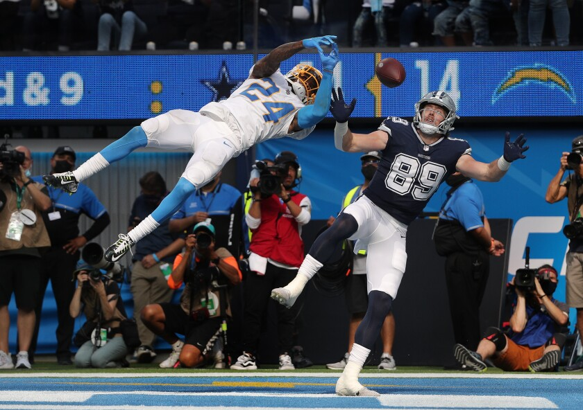 Chargers' Nasir Adderley leaps to break up a potential touchdown pass to Dallas Cowboys tight end Blake Jarwin.