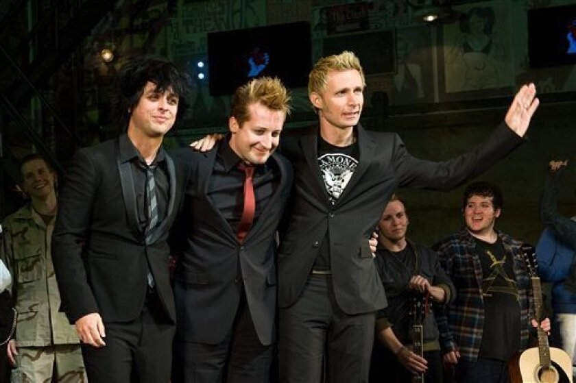 FILE - In this April 20, 2010 file photo, Green Day members, from left, Billy Joe Armstrong, Tre Cool and Mike Dirnt appear at the curtain call for the opening night performance of the Broadway musical 'American Idiot' in New York. (AP Photo/Charles Sykes, file)