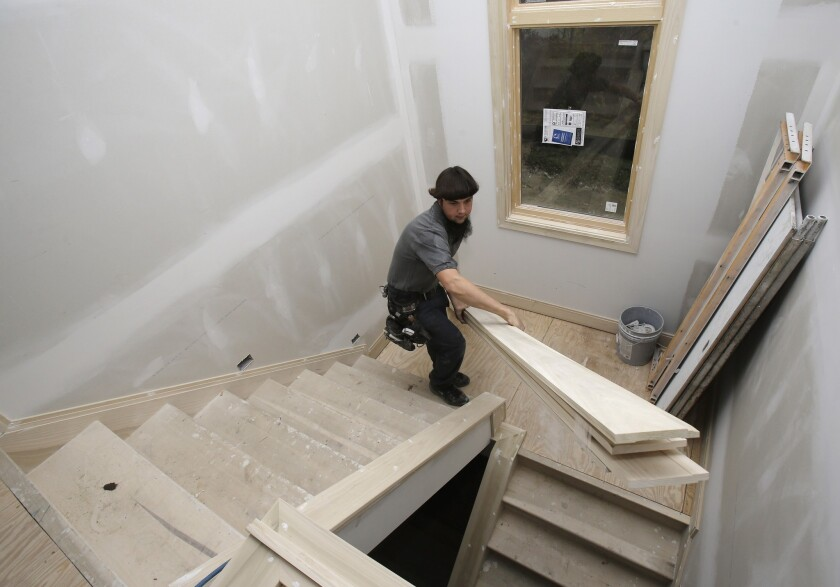 U.S. residential building permits hit a five-year high in October, the Commerce Department reported Tuesday. Above, a carpenter carries trim downstairs in a new home under construction in Pepper Pike, Ohio.