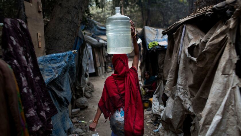 An Indian woman carries a plastic container filled with water in a slum area of New Delhi.
