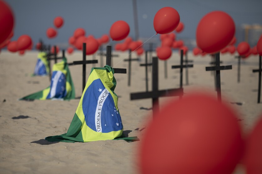 Crosses, red balloons and Brazilian flags honor victims of COVID-19.