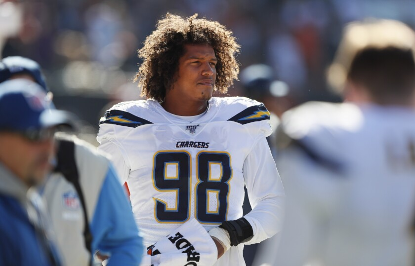 Chargers defensive lineman Isaac Rochell looks on from the sidelines during a game.